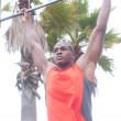 Portrait of an African American athlete doing pullups - Stock Photo