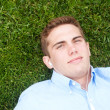 Young man lying in grass — Stock Photo