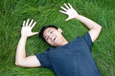 Young male asian student lying in the grass — Stock Photo