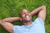 African American man lying in grass listening to music — Stockfoto