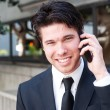 Portrait of handsome, young business man using cell phone, smiling — Stock Photo