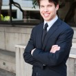 Portrait of a young businessman in suit standing outdoors — Stock Photo #9842589