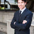 Portrait of a young businessman in suit standing outdoors — Stock Photo