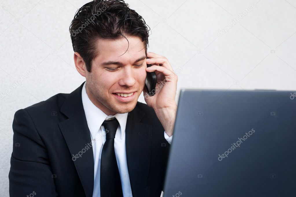 A young businessman on laptop talking on the phone — Stock Photo #9842537