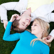 Stock Photo: Young couple in love lying in grass