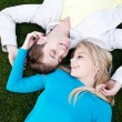 Young couple in love lying in grass — Stock Photo #9882017