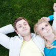Young couple in love lying in grass — Stock Photo