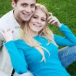 Young couple in love sitting in grass — Stock Photo