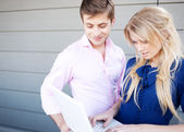 Portrait of a happy young professional couple using laptop standing outside — Stock Photo