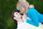 Young happy couple in love lying in grass — Stock Photo