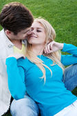 Young couple in love sitting in grass — Стоковое фото