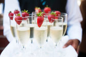 Waiter serving champagne on a tray — Stock Photo