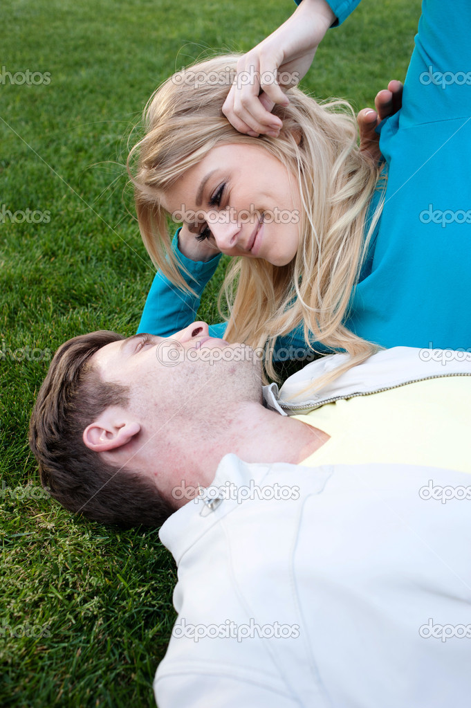 Young happy couple in love lying in grass  Stock Photo #9882037