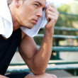 Portrait of a young athletic man with workout towel - Stock Photo