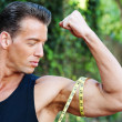 Muscular man measuring bicep — Stock Photo