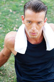 Portrait of a young athletic man with workout towel — Stock Photo