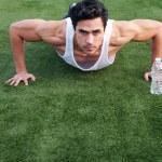 Handsome, young latino athlete doing push ups — Stock Photo #9961757