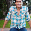 Happy young man sitting in a park — Stock Photo #9961837