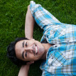 Happy young man lying in the grass — Stock Photo