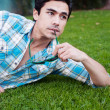 Handsome young man lying in the grass — Stock Photo #9961847