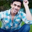 Handsome young man sitting in the grass — Stock Photo #9961849