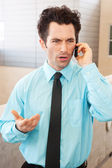 Frustrated executive on cell phone — Stockfoto