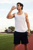 Jovem macho latino atleta água potável — Fotografia Stock