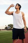 Young male latino athlete drinking water — Stock Photo