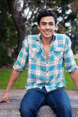 Happy young man sitting in a park — Stockfoto