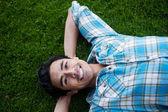 Mutlu genç adam çimlere yatan — Stok fotoğraf