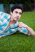 Handsome young man lying in the grass — Stock Photo