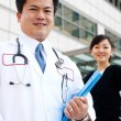 Asian doctor with nurse in background — Stock Photo
