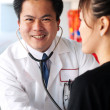 Asian doctor with stethoscope checking on patient — Stock Photo