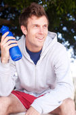 Portrait of a handsome young athlete with water bottle — Stock Photo
