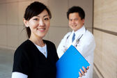 Asian nurse with doctor in background — Stock Photo