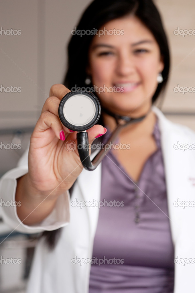 Portrait of young female doctor holding stethoscope  Stock Photo #9975390