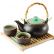 Brown teapot and teacups on the wooden trivet - Stock Photo