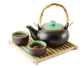 Brown teapot and teacups on the wooden trivet — Stock Photo