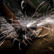 Spinning disk of circular saw with sparks - Stock Photo