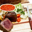 Rare steak with grilled vegetables on wooden plate — Stock Photo