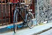 A black bike and urban graffiti in Melbourne — Stock Photo