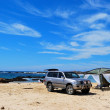 An off-road vehicle and a camping tent on a beach - Stock Photo