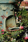 Plant and flower covered drinking fountain — Стоковое фото