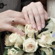Stock Photo: Hands of newlywed couple with bouquet