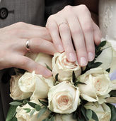 Hands of newlywed couple with bouquet — Stock Photo