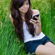 Asian cute girl texting on meadow — Stock Photo #10480806