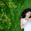 Asian cute girl texting on meadow - Stock Photo