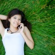 Asian girl on phone lying on a meadow — Stock Photo #10488149