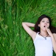Stock Photo: Asigirl lying on meadow and yawn