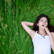 Asian girl lying on a meadow and yawn — Stock Photo